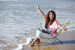 girl on beach with laptop