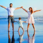 Happy family on beach dancing in Australia